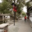 Royalty-Free Stock Photo: China, Shanghai, watertown of Zhujiajiao, also known as Shanghais Venice, street along the canal, lady bicycling