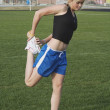 Teen girl stretching before running track — Stock Photo
