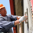 Stock Photo: Mason Worker Plastering Wall