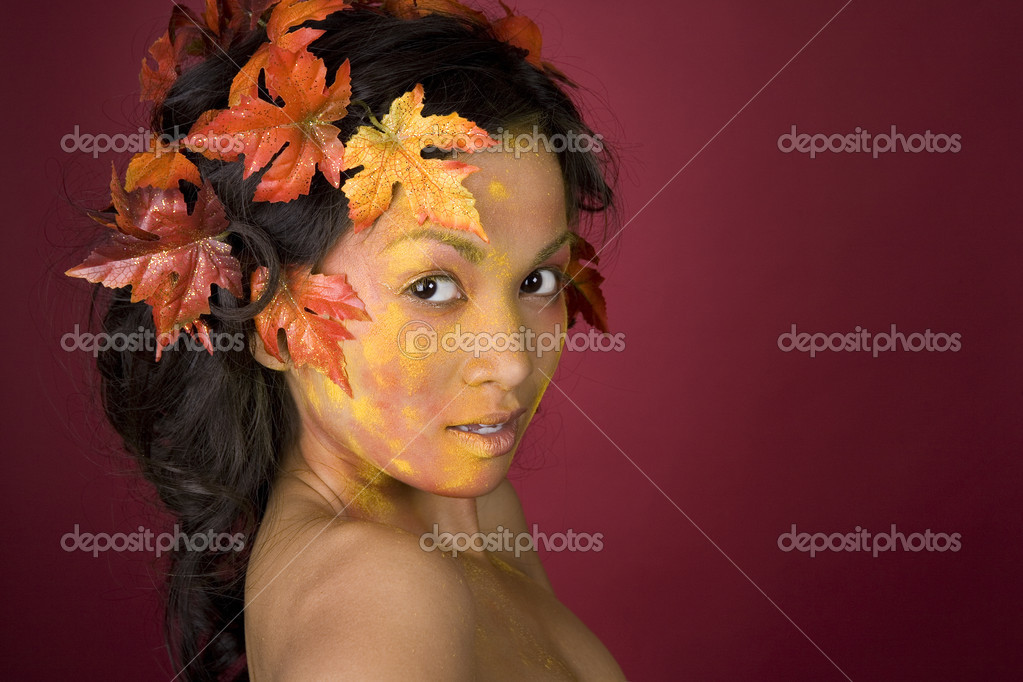Pretty brunette woman wearing leaves and colorful makeup — Stock Photo #9758851