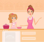 Happy mother helping her daughter cooking in the kitchen — Stock Photo