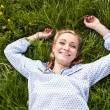 Young woman lying in green gras happy — Stock Photo