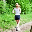 Young woman is jogging in forest — Stock Photo #10504905