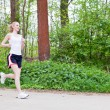 Young woman is jogging in forest — Stock Photo