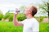 Young jogger is drinking water outdoor — Stock fotografie
