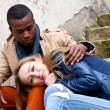 Young happy couple is sitting outside ethnicity — Stock Photo