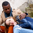 Stock Photo: Young happy couple is sitting outside ethnicity
