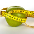 Fresh green apple with yellow measure tape — Stock Photo