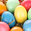Royalty-Free Stock Photo: Eastern eggs in different colours in a basket with a rabbit