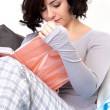 Stock Photo: Beautiful woman is sitting on the sofa an reading a book