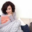 Beautiful woman is sitting on the sofa an reading a book - 图库照片