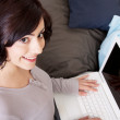 Young beautiful brunette woman is sitting on a sofa with a notebook — Stock Photo