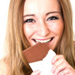 Young beautiful woman with a bright smile is eating chocplate — Stock Photo