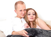 Young happy couple lying on the sofa and watching tv — Stock Photo