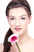 Young beautiful brunette woman with flower — Stock Photo