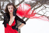 Beautiful woman with dark hair and red lips in white snow — Stock Photo