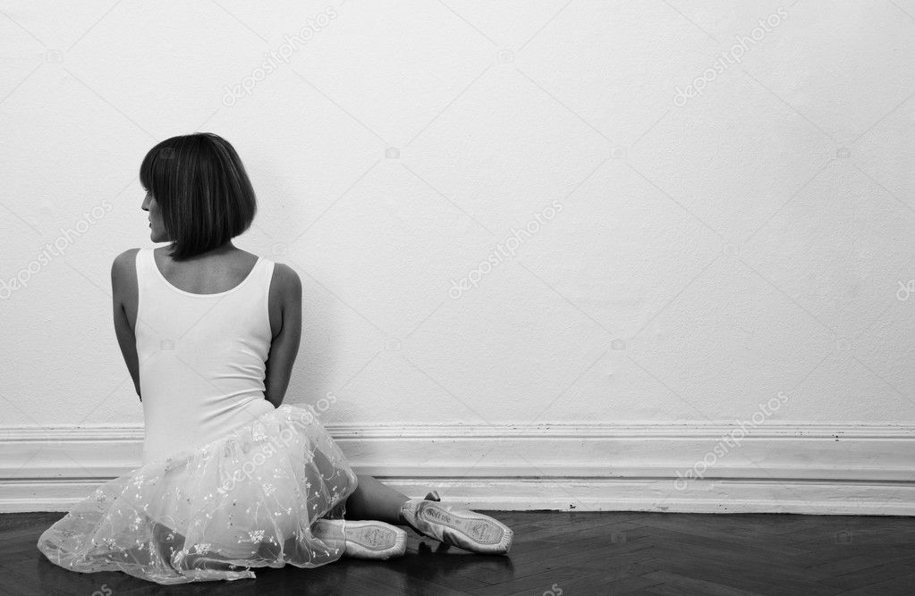 Beautiful ballerina is sitting on the floor in black and white — Stock Photo #9468899