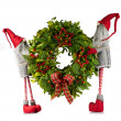 Christmas wreath carried by elves - Stock Photo