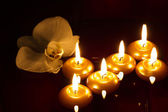 Floating candles and orchid in dark — Stock Photo