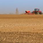 landbouw trekker zaaiend zaden en het cultiveren van veld — Stockfoto