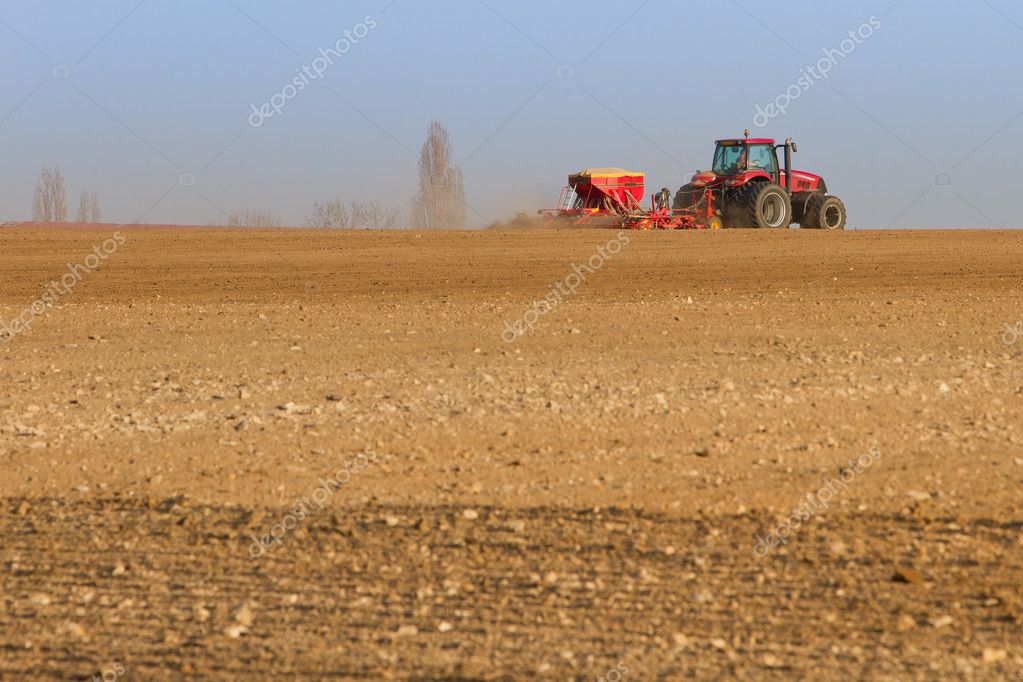 Agriculture tractor sowing seeds and cultivating field (focus on tractor)  Stock Photo #9607139