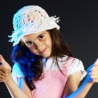 Little girl with a hat making OK sign, black background — Stock Photo