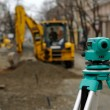 Theodolite and excavator - Stock Photo