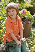 Little boy in rose garden — Stock Photo