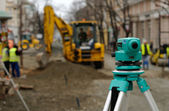 Theodolite and excavator — Stock Photo