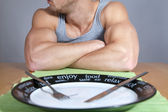 Muscular man with empty plate — Stock Photo