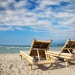 Wooden deckchairs on empty beach — 图库照片