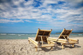 Wooden deckchairs on empty beach — Stock Photo