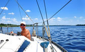 A yachtsman ruddering a boat — Stock Photo