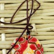 Red and yellow clay amulet - Stock Photo