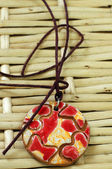 Red and yellow clay amulet — Stock Photo