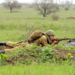 Soviet soldier of WW2 shooting in the field — Stockfoto