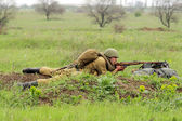 Soviet soldier of WW2 shooting in the field — Stock Photo