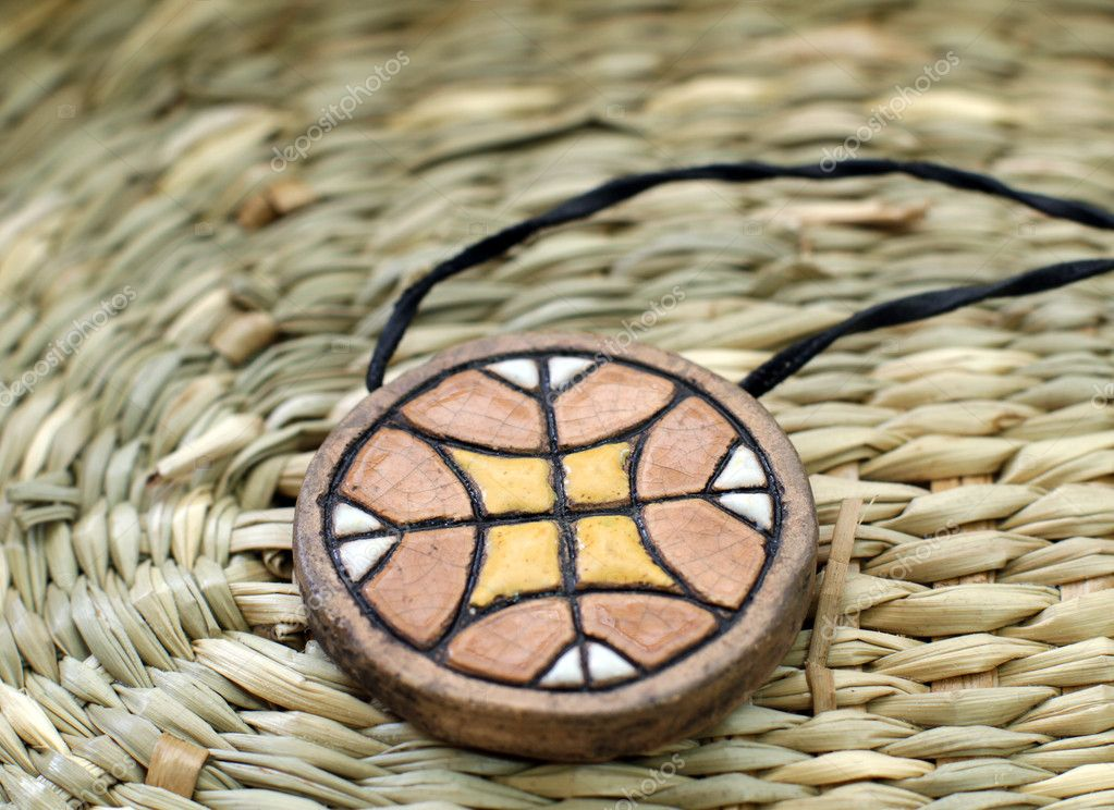 Ethnic handmade clay amulet on the wooden table — Stock Photo #9728547