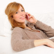 Woman speaking on the phone on a sofa — Stock Photo #9116379