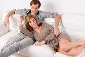 Couple smiling on white sofa — Stockfoto
