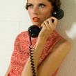 Girl calling on a old telephone dressed in orange on a sofa — Stock Photo