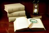 Books with magnifying glass and hourglass — Stock Photo