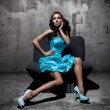Stunning brunette sitting and posing on a chair in fashion dress — Stock Photo #9077532