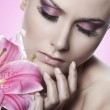 Beautiful fresh woman with lilies on pink background — Stock Photo