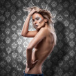 Beautiful blond woman whit diamonds posing on wall — Stock Photo