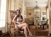 Attractive Caucasian woman sitting in retro decorated room — Stock Photo