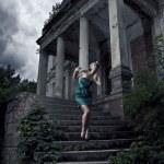Beautiful blonde woman posing near the dark castle — Stock Photo