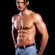 Handsome powerful muscular man isolated on black — Stock Photo