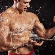 Muscular man having shower - 