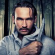 Man with a knife in a dark forest - Stock Photo